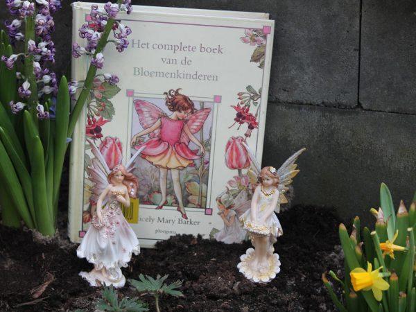 Bloemenkinderen in tuin met beeldjes